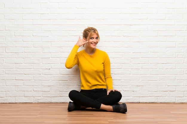 Young girl sitting on the floor making phone gesture. call me back sign Premium Photo