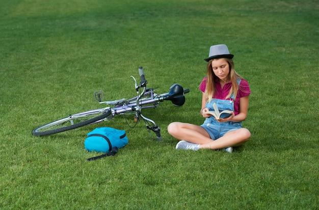 草の上にbycicleの近くに座っている少女。 Premium写真