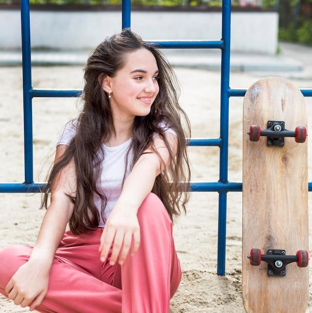 スケートボードの隣に座っている若い女の子 無料写真