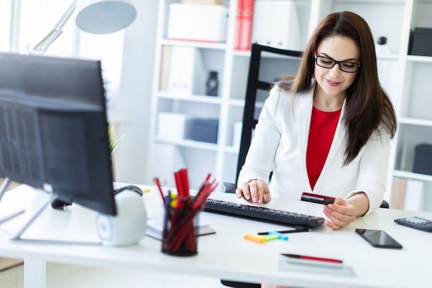 A young girl sitting in the office at the table and holding a bank card. Premium Photo