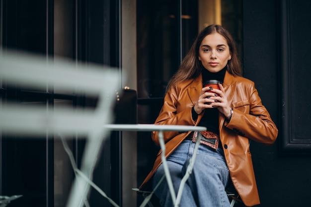 Молодая девушка сидит возле кафе и пьет кофе Бесплатные Фотографии