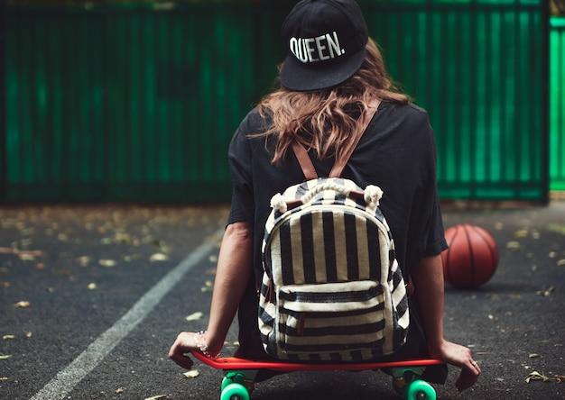 Young girl sitting on plastic orange penny shortboard on asphalt in cap Free Photo