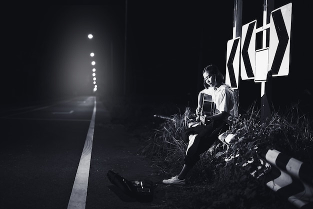 Young girl sitting and playing guitar on road side with road sign background, journey of musician concept Premium Photo