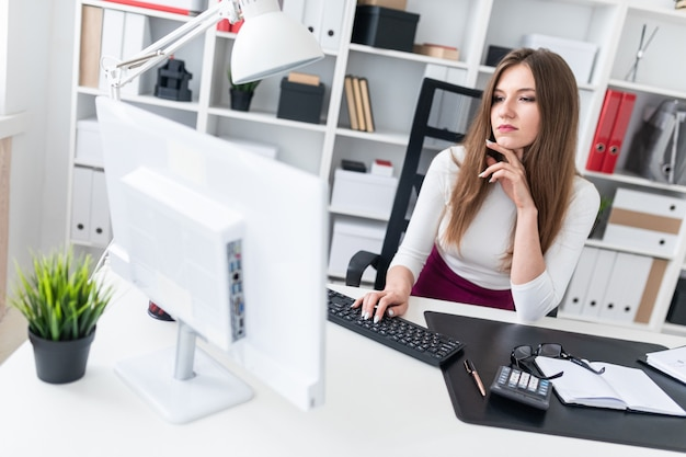A young girl sitting at a table and typing on the keyboard. Premium Photo