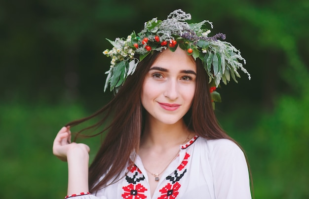 A young girl of slavic appearance with a wreath of wild flowers on the midsummer. Premium Photo