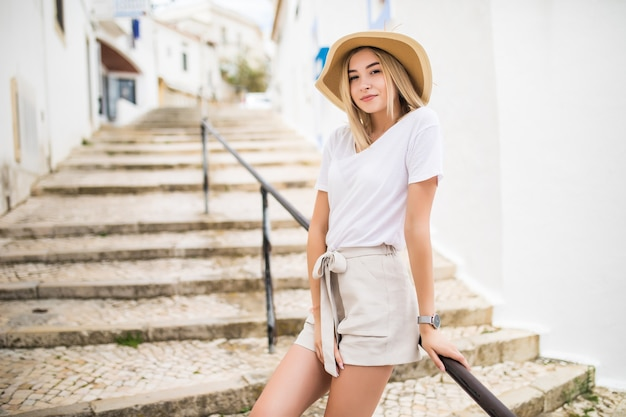 Giovane ragazza in piedi sulle scale di pietra e corrimano in strada in estate Foto Gratuite