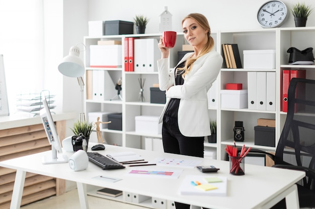 A young girl stands in the office near a computer desk and holds a red cup in her hands. Premium Photo