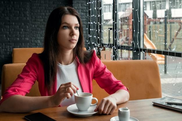 A young girl stirs sugar in a cup of coffee, sits in a cafe behind a wooden stolikos Premium Photo