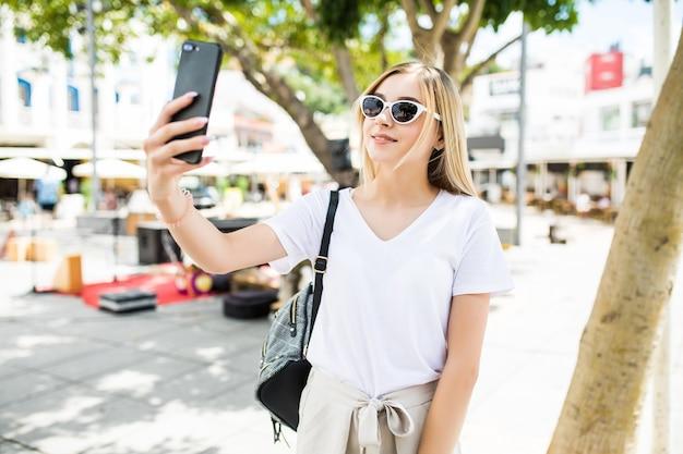Молодая девушка принимает селфи из рук с телефоном на улице летнего города. Бесплатные Фотографии