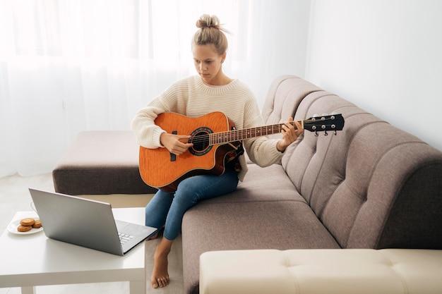 온라인 기타 레슨을받는 어린 소녀 프리미엄 사진