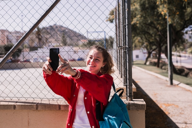 Young girl taking photo by smartphone near sportsground Free Photo
