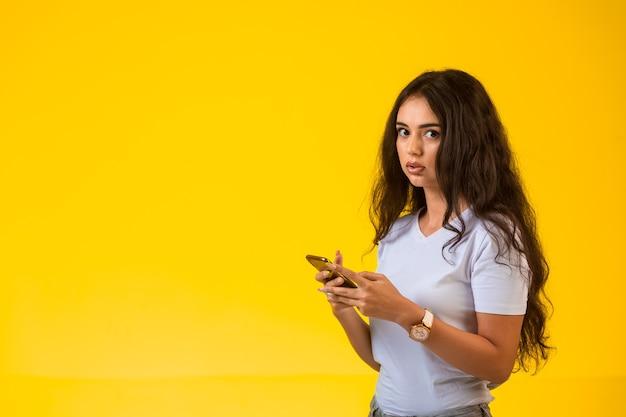 Молодая девушка разговаривает и болтает по телефону, глядя в сторону. Бесплатные Фотографии