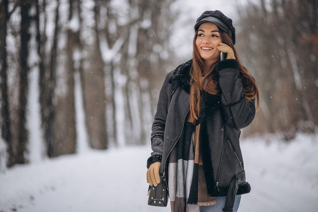 Young girl talking on the phone in a winter park Free Photo