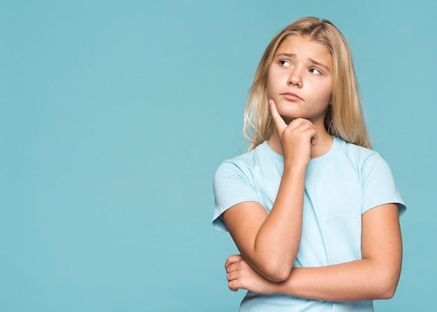 Молодая девушка думает с копией пространства Бесплатные Фотографии