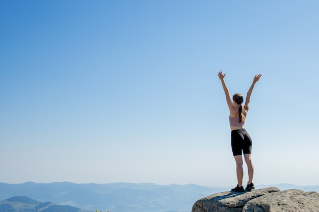 The young girl at the top of the mountain raised her hands up on blue sky. the woman climbed to the top and enjoyed her success. back view. Premium Photo