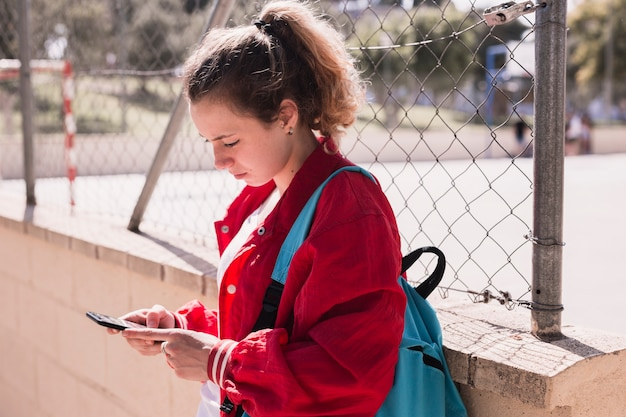 Young girl typing text at smartphone near sportsground Free Photo