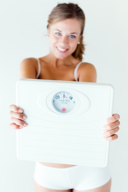 Young girl in underwear holding scales. Free Photo