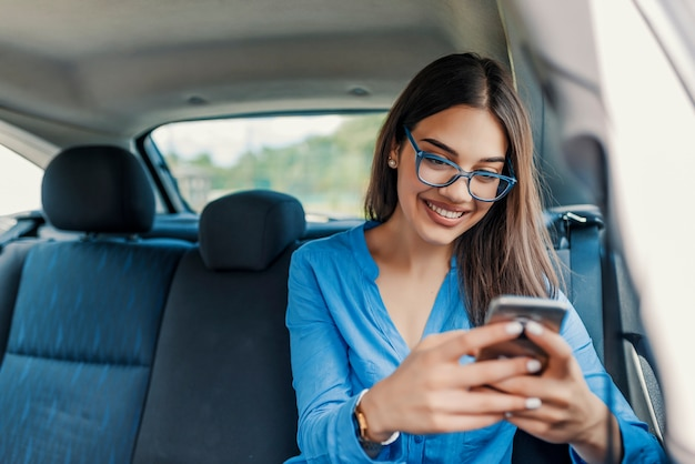Young girl uses a mobile phone in the car. technology cell phone isolation Premium Photo