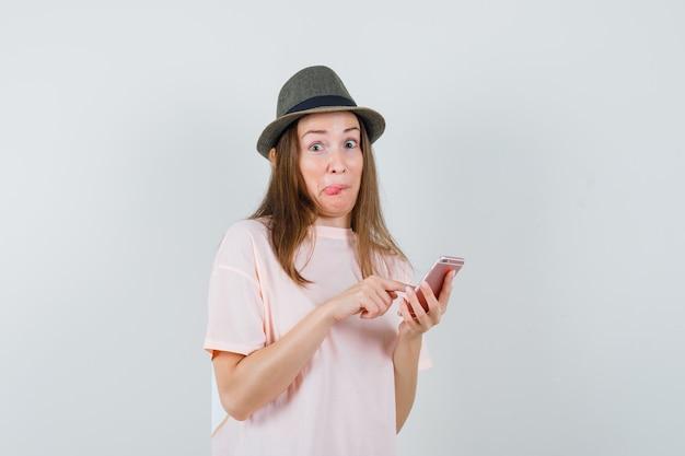 ピンクのtシャツ、帽子、好奇心旺盛に見える携帯電話を使用して若い女の子。正面図。 無料写真