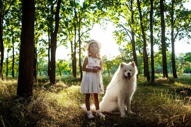 Молодая девушка гуляет, играя с собакой в парке на закате. Бесплатные Фотографии