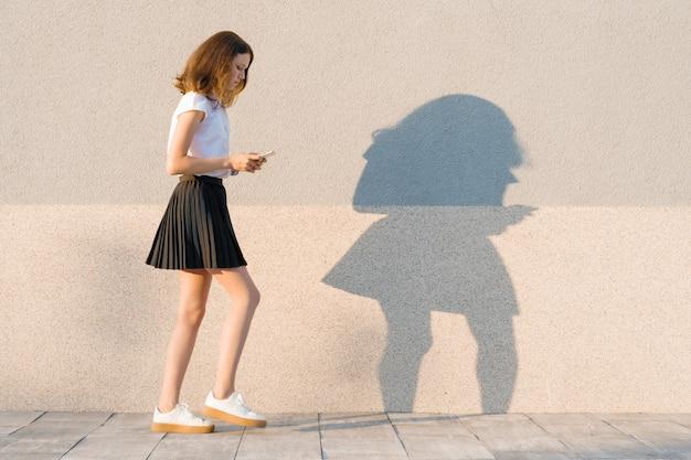 大きなステップで歩くと携帯電話でテキストを読む少女 Premium写真