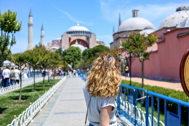 A young girl walks towards aya sofia. rear view. turkey. istanbul Premium Photo