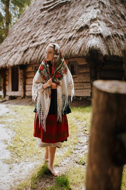 Young girl walks in the village in a traditional ukrainian dress Free Photo