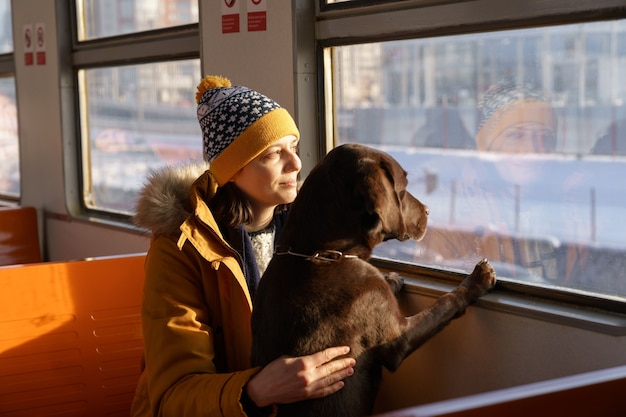 Young girl wear winter clothes sitting in local train with her lovely dog looking through the window Premium Photo
