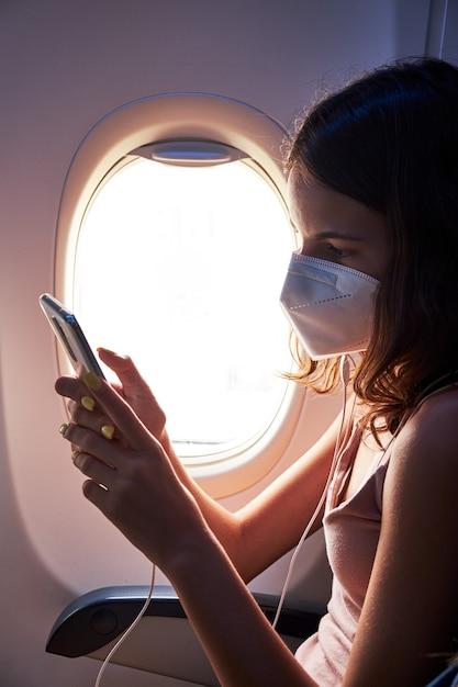 Молодая девушка в маске для лица с помощью смартфона во время путешествия на самолете Premium Фотографии