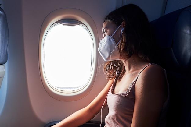 Молодая девушка в маске для лица во время путешествия на самолете Premium Фотографии