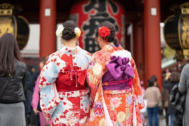 Маленькая девочка нося японское кимоно стоя перед виском sensoji в токио, японии. Premium Фотографии