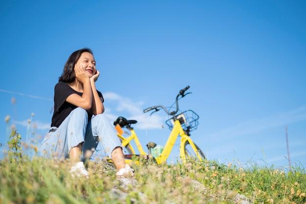 Молодая девушка в джинсовой черной футболке сидит с велосипедом в парке с голубым небом Premium Фотографии
