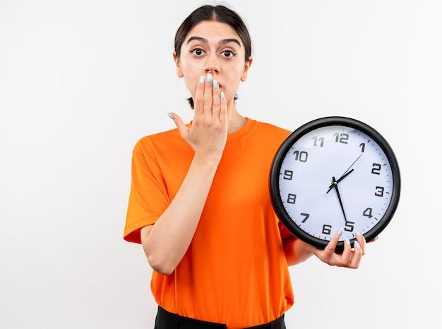 Giovane ragazza che indossa la maglietta arancione che tiene l'orologio da parete che è scioccato che copre la bocca con la mano in piedi sul muro bianco Foto Gratuite