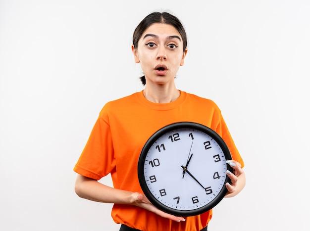 Giovane ragazza che indossa la maglietta arancione che tiene orologio da parete lookign alla telecamera essendo sorpreso e confuso in piedi su sfondo bianco Foto Gratuite