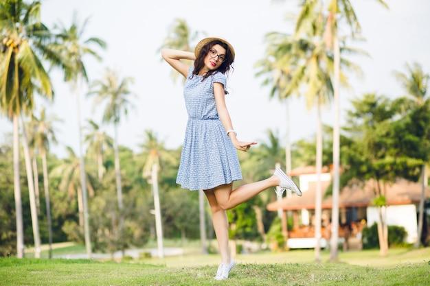 Молодая девушка в голубом платье стоит на одной ноге на цыпочках в парке. на девушке соломенная шляпа и черные очки. Бесплатные Фотографии