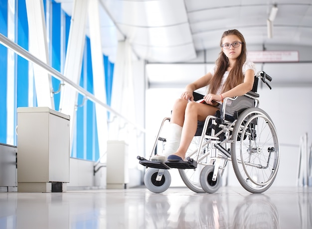 A young girl in a wheelchair is reading a book, patient in a wheelchair in the hospital corridor. Premium Photo