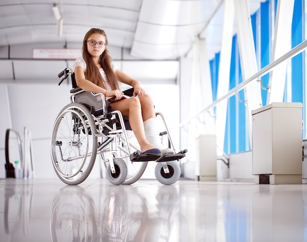 A young girl in a wheelchair is reading a book. patient in a wheelchair in the hospital corridor. Premium Photo
