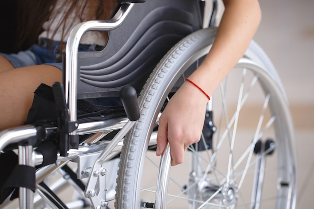 A young girl in a wheelchair is standing in the corridor of the hospital. Premium Photo