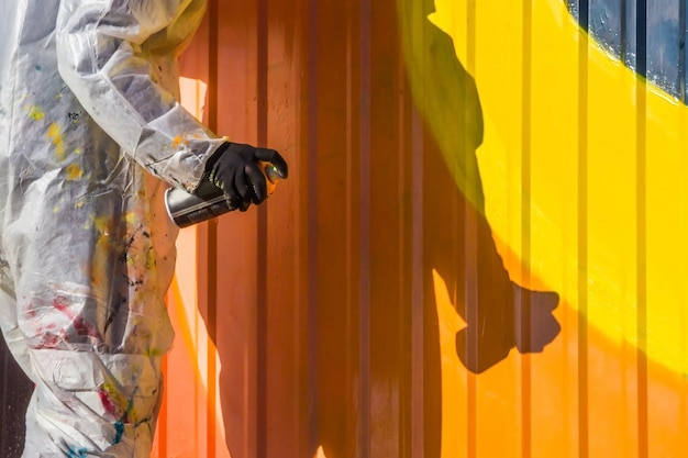 A young girl in a white coat with spots of paint paints ribbed iron fence graffiti Premium Photo