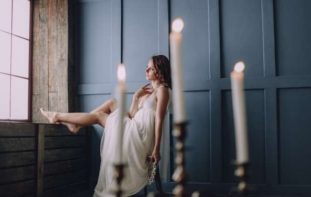 La ragazza in un vestito bianco dentro in una stanza si siede vicino ad una finestra Foto Gratuite
