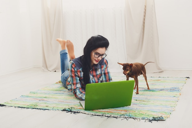Young girl on white sofa with a laptop Premium Photo