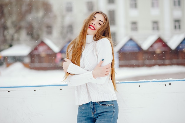 Young girl in a white sweater standing in a winter park Free Photo