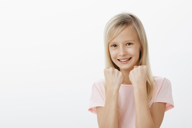 La ragazza mostrerà a tutti i suoi punti di forza. allegra adorabile figlia in maglietta rosa, alzando i pugni chiusi, in piedi in posa da boxe, scherzando e sorridendo ampiamente, difendendo Foto Gratuite