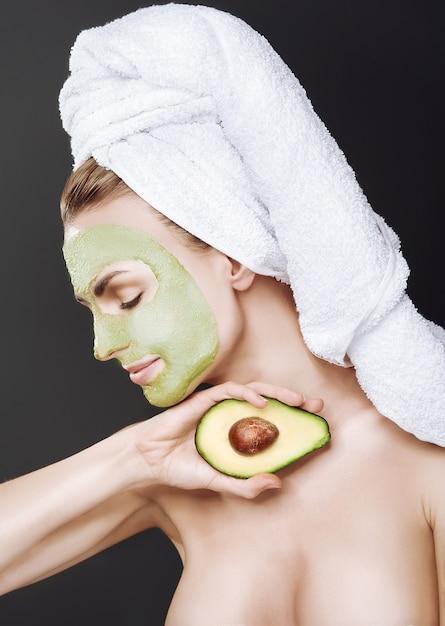 Молодая девушка с косметической маской из авокадо. темный фон, студийный свет. Premium Фотографии