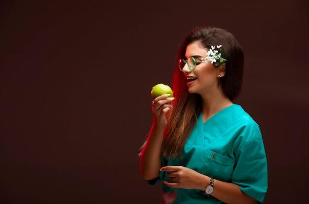 손에 녹색 사과와 물린 복용 어린 소녀. 무료 사진