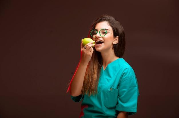 手に青リンゴを食べる少女。 無料写真