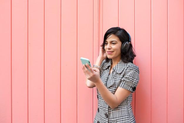 Молодая девушка с гарнитурой смотрит на свой мобильный телефон Premium Фотографии