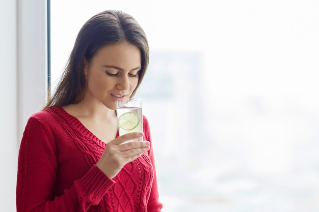 Young girl with aglass of water with lime Premium Photo