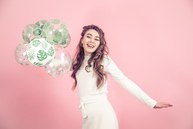 色の壁に風船を持つ少女 無料写真