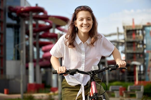 市内の自転車を持つ少女 Premium写真